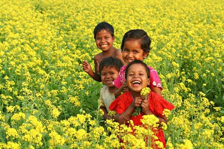 Crianças sorrindo em campo florido